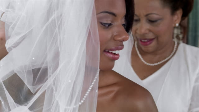 Mother helping bride get dressed before wedding