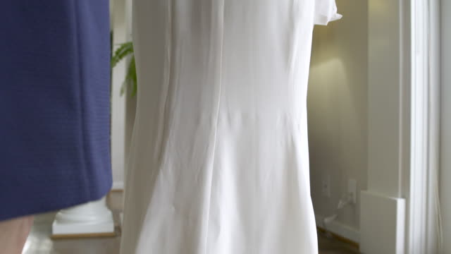 Mother helping bride into wedding dress.