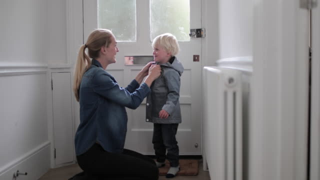 vidéos et rushes de mother helping child put on a coat - parents