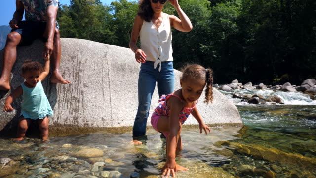 vídeos y material grabado en eventos de stock de ms mother helping daughter balance with playing in river with family on summer afternoon - menos de diez segundos