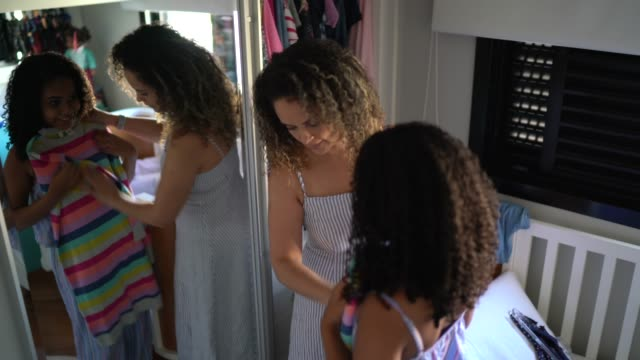mother helping daughter choosing clothes at home - wardrobe stock videos & royalty-free footage