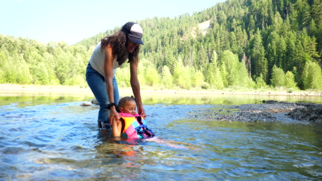 ms mother helping daughter float in river on summer afternoon - life jacket stock videos & royalty-free footage