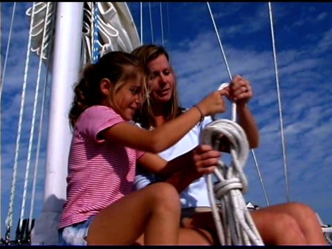 mother helping daughter on sailboat - tre quarti video stock e b–roll