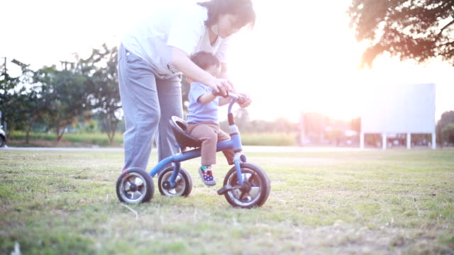mother helping daughter ride tricycle - tricycle stock videos & royalty-free footage