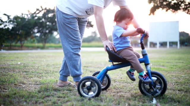 mother helping daughter ride tricycle. - tricycle stock videos & royalty-free footage