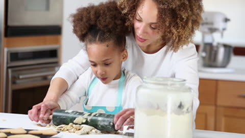 ms mother helping daughter roll dough in kitchen to bake cookies / richmond, virginia, united states - baked stock videos & royalty-free footage