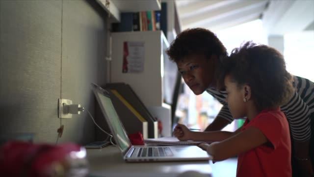 stockvideo's en b-roll-footage met moeder die dochter met huiswerk helpt - thuisonderwijs