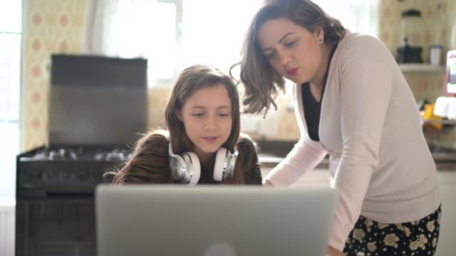 vidéos et rushes de mère aidant la fille avec des devoirs à la maison - utilisant l'ordinateur portatif et faisant un chat vidéo - filmer