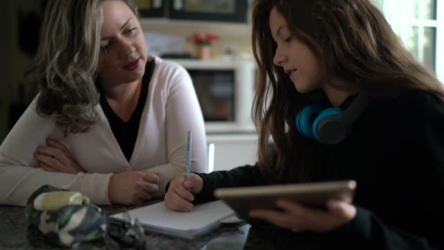 vídeos de stock, filmes e b-roll de mãe ajudando filha com lição de casa - família monoparental