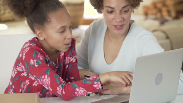 mother helping daughter with homework online - e learning stock videos and b-roll footage
