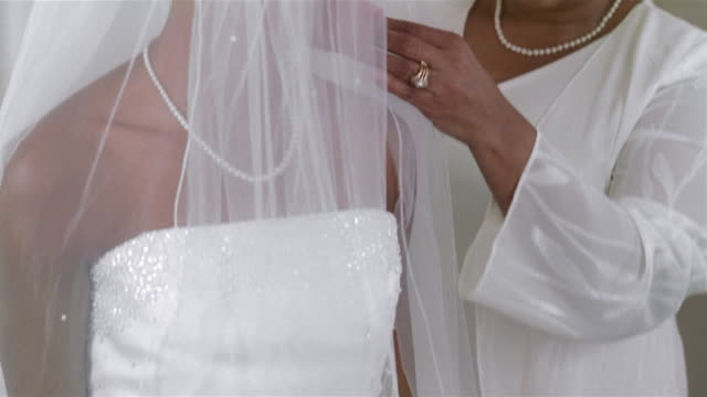 mother helping daughter with veil before wedding - bride stock videos & royalty-free footage