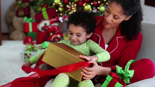 vidéos et rushes de ms mother helping excited young daughter open christmas present / richmond, virginia, united states - prendre sur les genoux