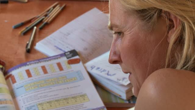 CU Mother helping girl doing math school work at home / San Pedro de Atacama, Norte Grande, Chile