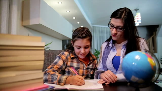 mother helping happy daughter with homework - family with one child stock videos & royalty-free footage