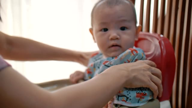 mother helping her baby boy sitting on high chair - potassium stock videos & royalty-free footage