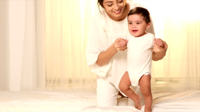 cu mother helping her baby girl to walk on bed / delhi, india - baby girls stock videos & royalty-free footage