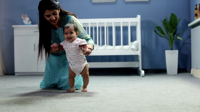 mother helping her baby walk  , delhi, india - babygro stock videos & royalty-free footage