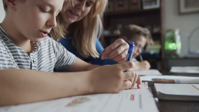 mother helping her children to do the homework - quaderno video stock e b–roll