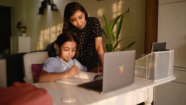 mother helping her daughter during her e-learning session - indian ethnicity stock videos & royalty-free footage