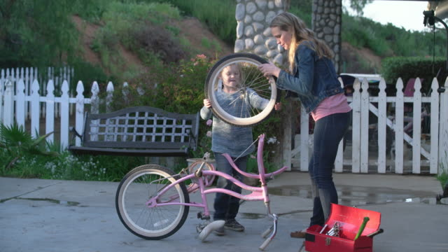 MS Mother helping her daughter how to fix a bicycle