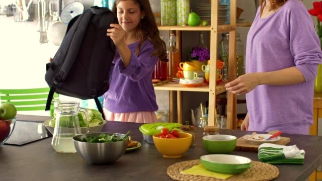 vídeos y material grabado en eventos de stock de madre ayudando a su hija a empacar la lonchera en su espalda - rucksack
