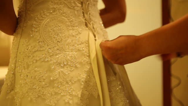Mother helping her daughter to dress up bridal dress
