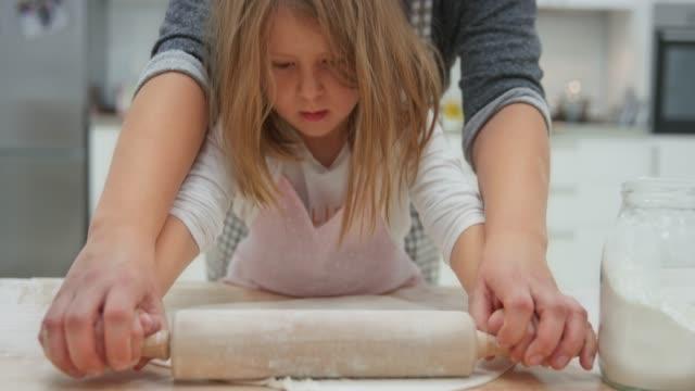 vídeos de stock e filmes b-roll de mother helping her small daughter roll out the pizza dough - feito em casa