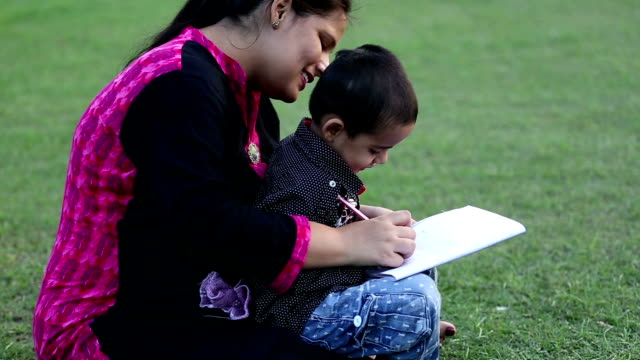 mother helping her son in doing school homework - note pad stock videos & royalty-free footage