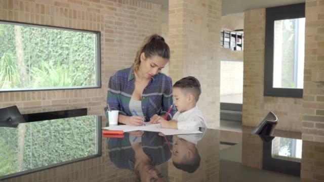 vidéos et rushes de mère aidant son fils à faire des devoirs - son