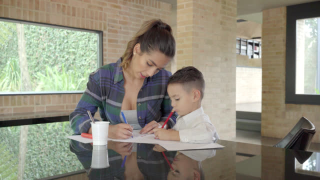 mother helping her son to do homework - single mother stock videos & royalty-free footage