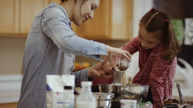 vídeos de stock e filmes b-roll de mother helping her young daughter measure chocolate chips - medir
