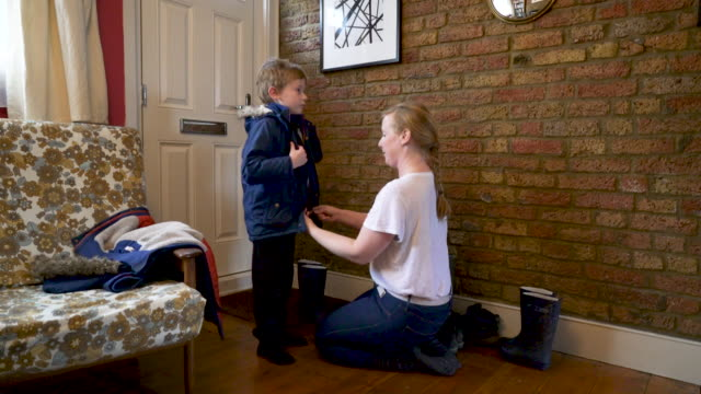 stockvideo's en b-roll-footage met a mother helping her young son get his coat and wellington boots on - rubberlaars
