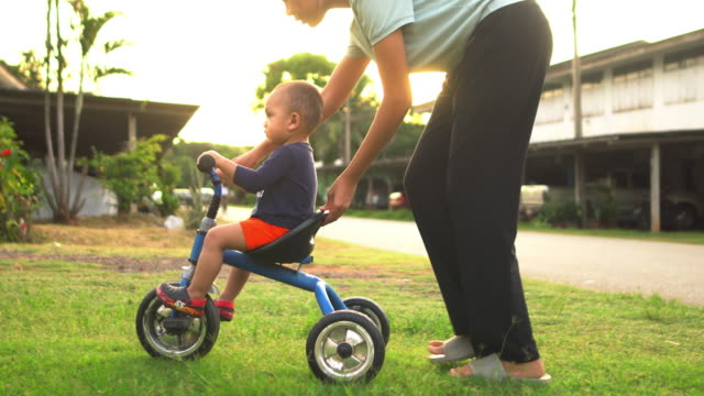 mother helping little boy ride tricycle - tricycle stock videos & royalty-free footage