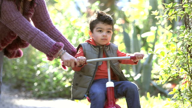 mother helping little boy ride tricycle - toddler stock videos & royalty-free footage