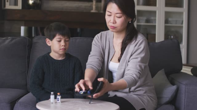 mother helping son check blood sugar levels - type 1 diabetes stock videos & royalty-free footage