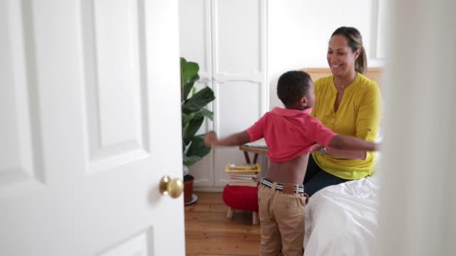 vídeos de stock, filmes e b-roll de mother helping son dress in the morning - camisas