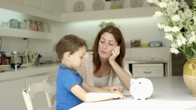 Mother helping son to save money in piggy bank.