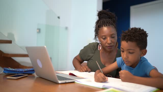 mother helping son using laptop on homeschooling - textbook stock videos & royalty-free footage