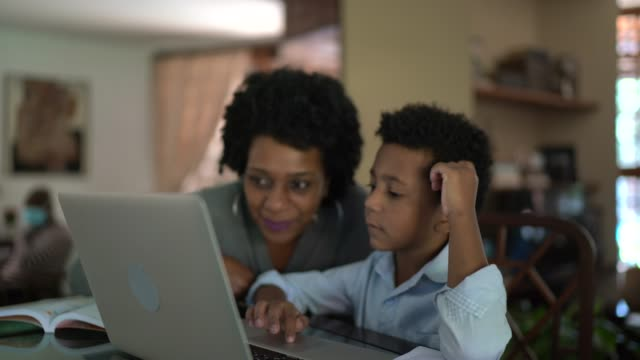 mother helping son while he is studying on laptop - development stock videos & royalty-free footage