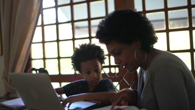 vídeos de stock, filmes e b-roll de mãe ajudando filho enquanto ele está estudando no laptop - distante