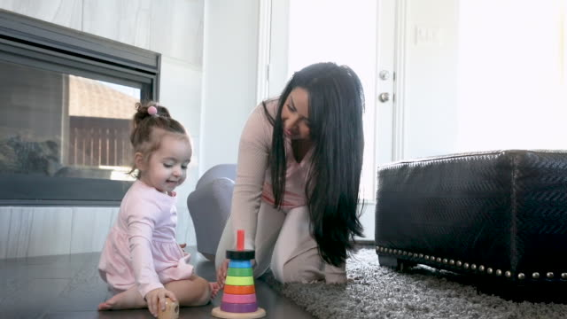 mother helping toddler daughter play with toys in living room floor - daughter stock videos & royalty-free footage