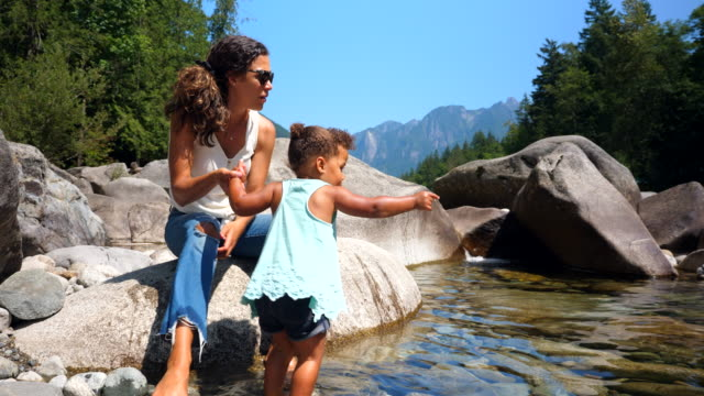 ms mother helping toddler daughter wade in river on summer afternoon - toddler stock videos & royalty-free footage