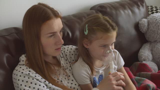 vidéos et rushes de la mère aide la fille à faire l'inhalation - inhalateur