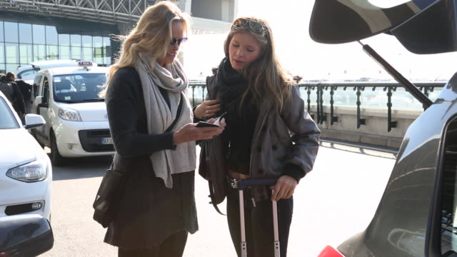 Mother helps daughter with passport/bag at airport