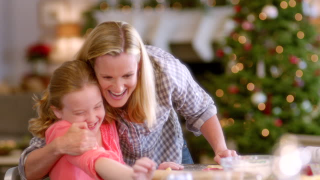 mother helps happy young girl place christmas tree-shaped cookie dough on baking sheet, hugs her proudly - baking sheet stock videos & royalty-free footage