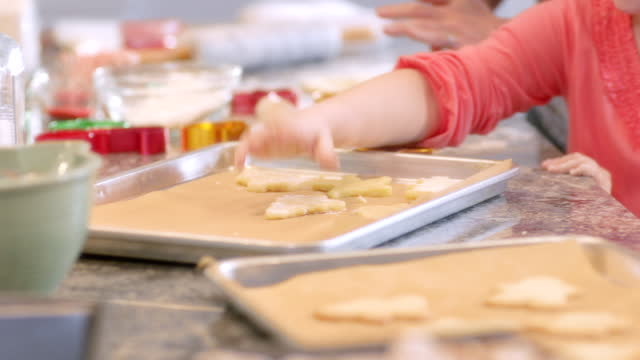 mother helps happy young girl place christmas tree-shaped cookie dough on baking sheet - baking sheet stock videos & royalty-free footage