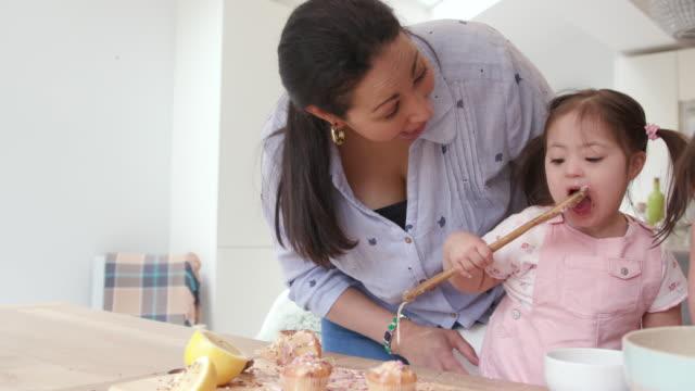 母親は彼女の若い娘がケーキの装飾のためにアイシングを混ぜるのに役立ちます - 依存点の映像素材/bロール