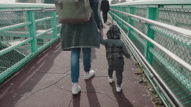 Mother hold hand of his son walking on sidewalk.
