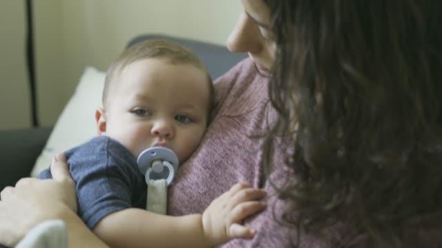 vídeos de stock, filmes e b-roll de mother holding baby against her chest. - bico