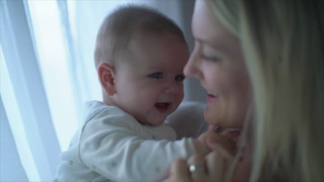 stockvideo's en b-roll-footage met cu sm mother holding baby at home - aanhankelijk